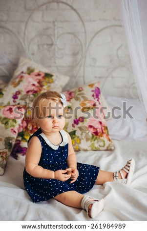 Little sitting on the bed - stock photo