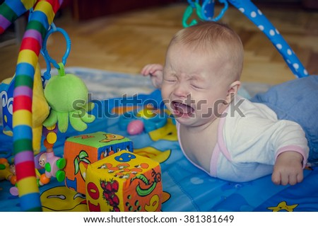 Little six months old baby boy crying bitterly, lying on his stomach on the play mat and looking on the toys. Kid getting frustrated with his little toys. Indoors. Selective focus. - stock photo