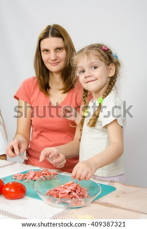 Little six year old girl helps mother to cook at the kitchen table