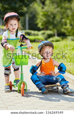 Little skateboarder sits on skateboard with his arms akimbo ,little girl with three-wheeled scooter stands next to him
