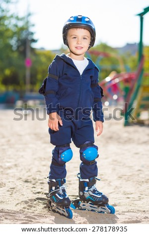 Little skater boy in helmet posing on the playground - stock photo