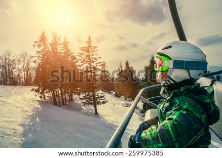 Little skier on the ski lift - stock photo