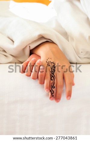 Little sleeping child hands with tattoo on white bed linen. Indoors closeup. - stock photo