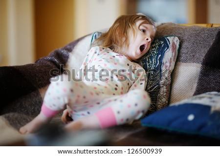 Little sleepy girl in pajamas yawning - stock photo