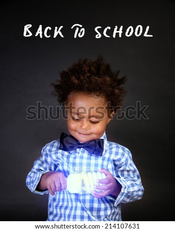 Little smart boy holding in hands bright electrical lamp isolated on black background, innovation in physic, back to school concept - stock photo