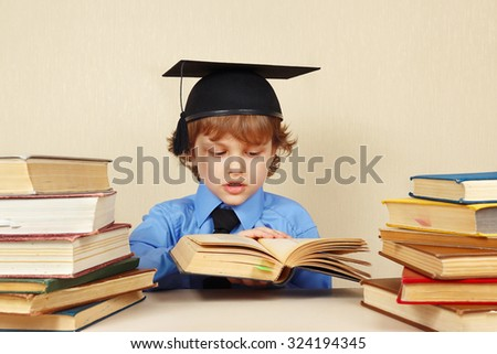 Little smart boy in academic hat turns the pages of an old book - stock photo