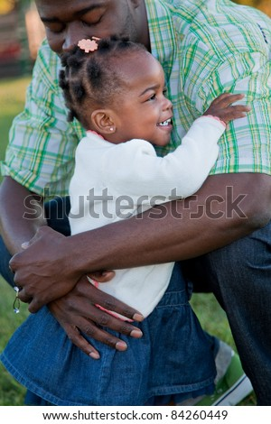 Little Smiling African American Girl Hugging Dad Outdoor - stock photo