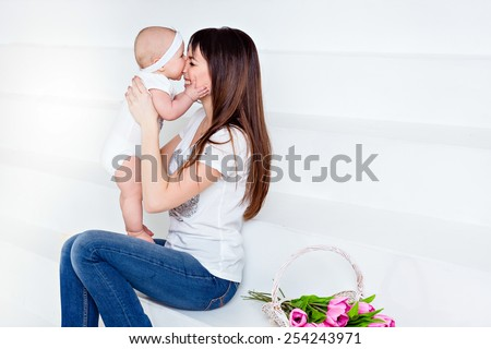 little smiling baby daughter bites his nose mom brunette in white t-shirt and jeans on a white background in the Studio, next to the tulips - stock photo