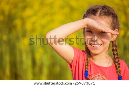 Little smiling beautiful girl closes her eyes from the sun, on a background of green summer city park. - stock photo