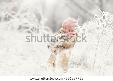 little smiling beautiful girl in beige oat and pink hat standing in the magic snowing winter forest or park and holding rabbit on hands - stock photo