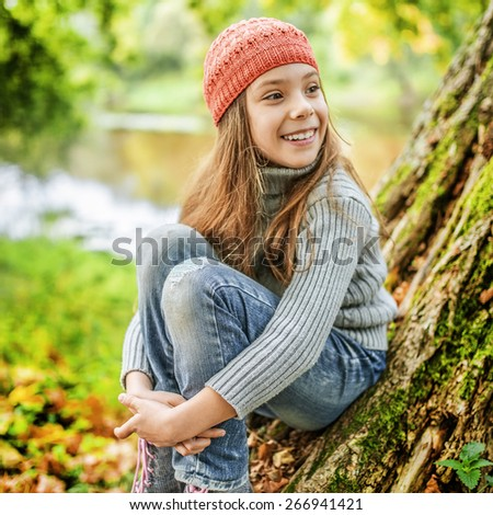 Little smiling beautiful girl in red hat sits on background of autumn nature. - stock photo