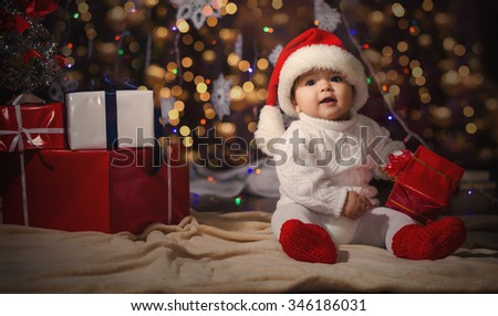 Little smiling boy (baby) in a white knitted sweater and hat of Santa Claus on a background of Christmas garland and gift boxes with ribbon. - stock photo