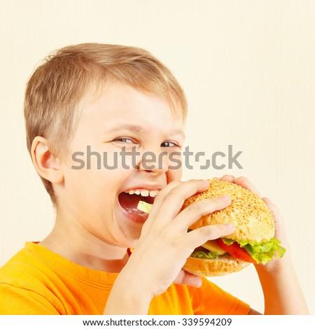 Little smiling boy eating a tasty hamburger - stock photo