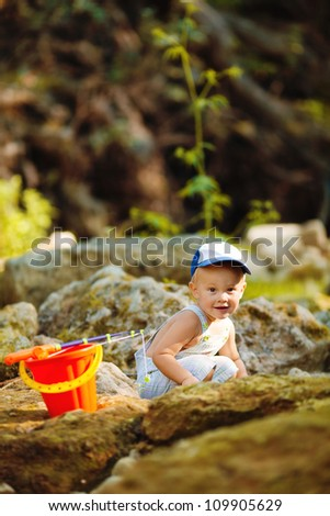 Little smiling boy fishing outdoors - stock photo