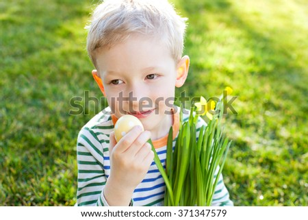 little smiling boy holding easter egg and blooming daffodils at spring time, spring and easter time concept