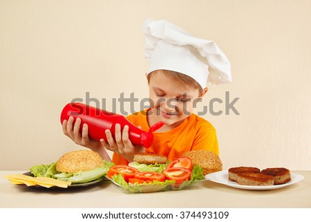 Little smiling boy in chefs hat puts sauce on the hamburger - stock photo