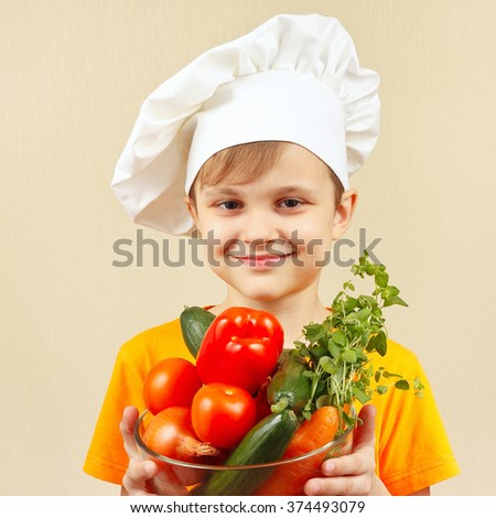 Little smiling boy in chefs hat with the fresh vegetables