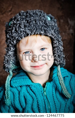 Little smiling boy in flapped knitted hat - stock photo