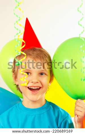 Little smiling boy in holiday hat with festive balls and a streamer