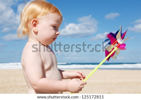 Little smiling boy is holding a pinwheel in front of the cloudy sky. - stock photo