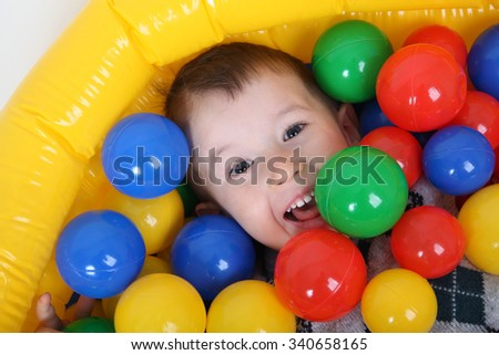 Little smiling boy playing in colorful balls playground - stock photo