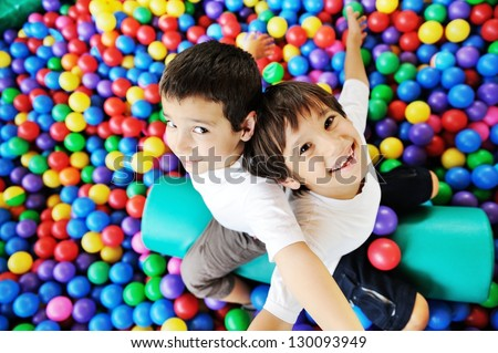 Little smiling boy playing lying in colorful balls park playground - stock photo