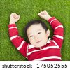 little smiling boy resting and hand up  in meadow - stock photo