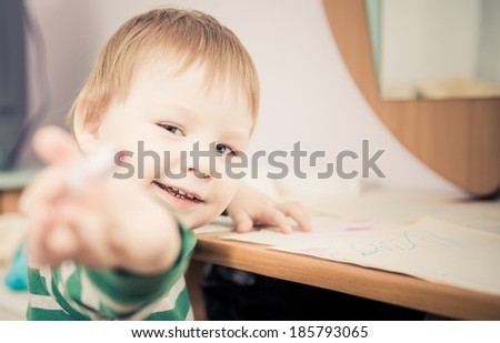 little smiling boy showing drawing pen