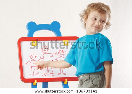 Little smiling boy shows his family painted on whiteboard - stock photo