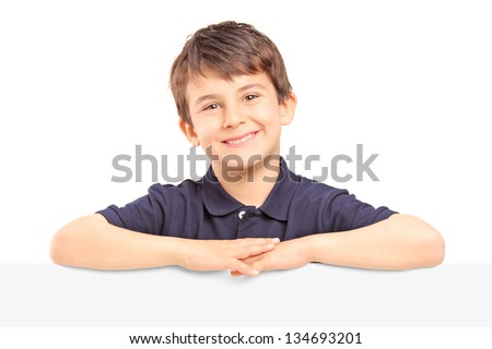 Little smiling boy standing behind a blank panel isolated on white background - stock photo