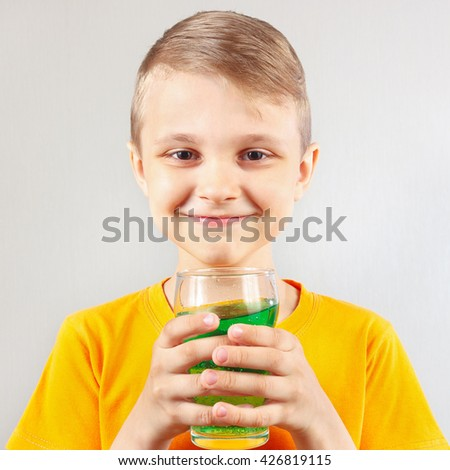 Little smiling boy with a glass of fresh green lemonade