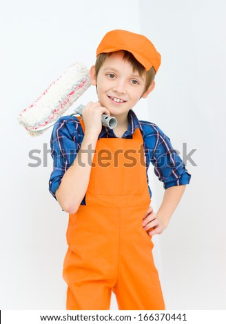 Little smiling builder in coveralls with paint roller