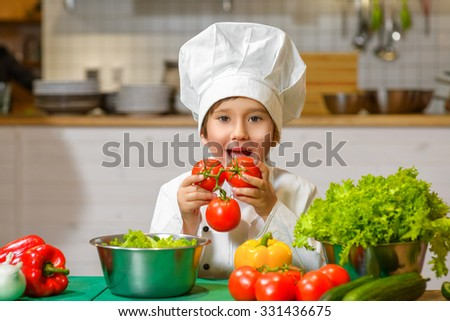 Little smiling Chef boy preparing healthy food at kitchen and going to try fresh tomatoes. the concept of vegetarianism - stock photo