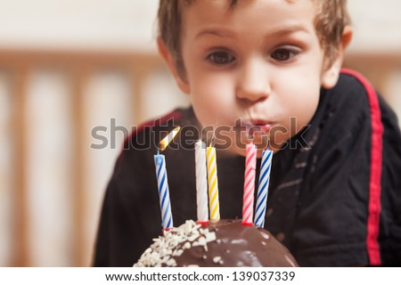 Little smiling child boy blowing birthday celebration sweet cake candle fire - stock photo