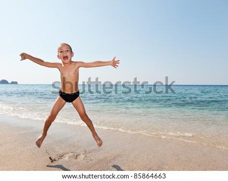 Little smiling child boy jumping on sea sand beach - stock photo