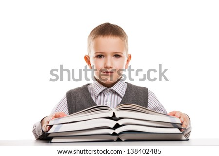 Little smiling child boy reading education books at desk - stock photo