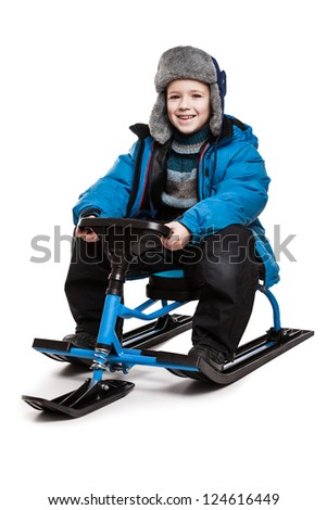Little smiling child boy sitting on snow scooter or snowmobile toy white isolated - stock photo