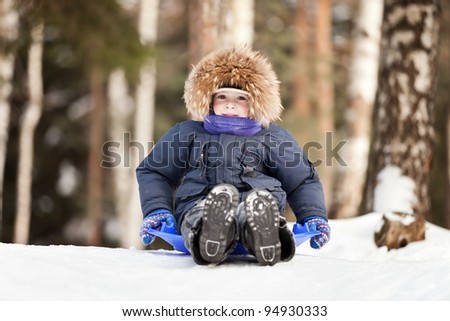 Little smiling child boy sled tobogganing on winter snow hill - stock photo
