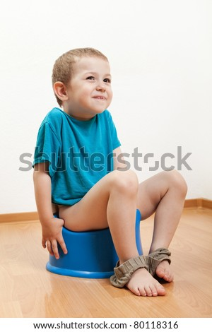 Little smiling child boy urinating toilet potty pan - stock photo