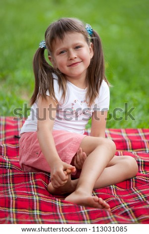 Little smiling cute blond girl preschooler with ponytails sitting on the red plaid on green grass in summer - stock photo
