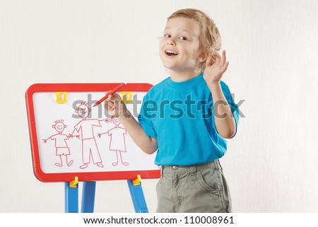Little smiling cute boy drew a family on whiteboard - stock photo