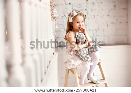 little smiling cute girl in beautiful dress is sitting with teddy bear in her hands - stock photo