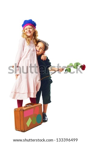 little smiling girl and boy embraced and stand with suitcase on white background - stock photo