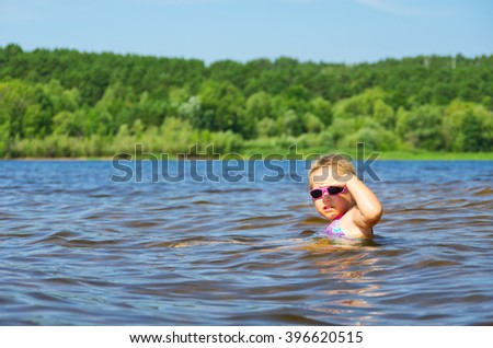 Little smiling girl at river