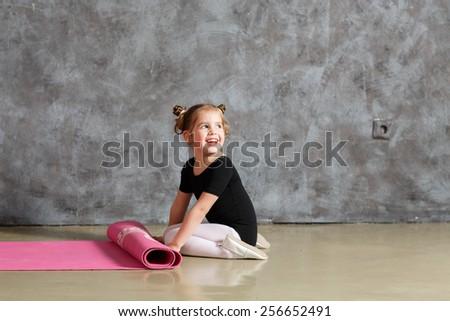 little smiling girl doing exercises  - stock photo