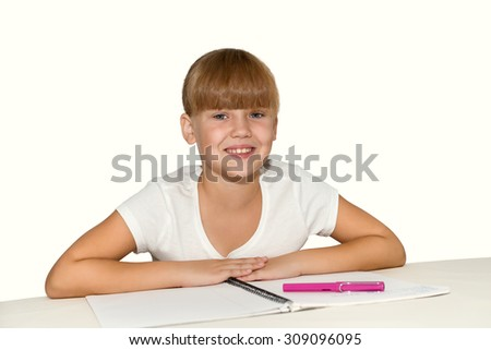 Little smiling girl doing homework at the desk isolated - stock photo