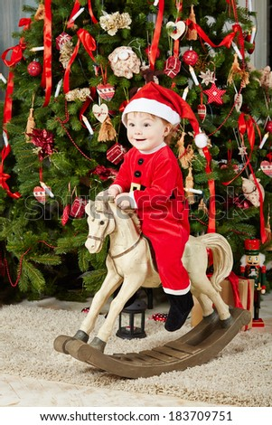 Little smiling girl dressed in santa suit sits on rocking horse under Christmas tree on furry rug - stock photo
