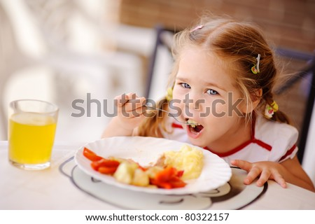 little smiling girl have a breakfast in outdoor cafe - stock photo