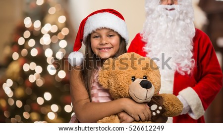 Little smiling girl holding a Christmas present in her house