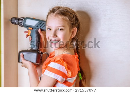 Little smiling girl holding a drill. - stock photo